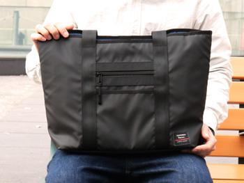 膝の上にがま口クラッチ付きトートバッグをのせている画像